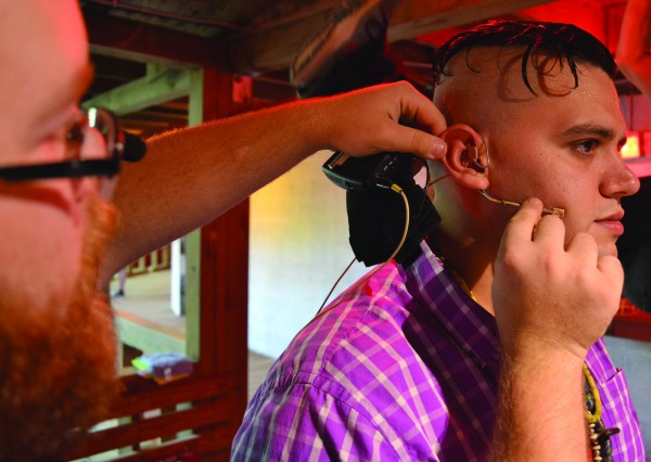 Sound Technician Josh Fronk places a microphone on Actor Kyle Streets.
