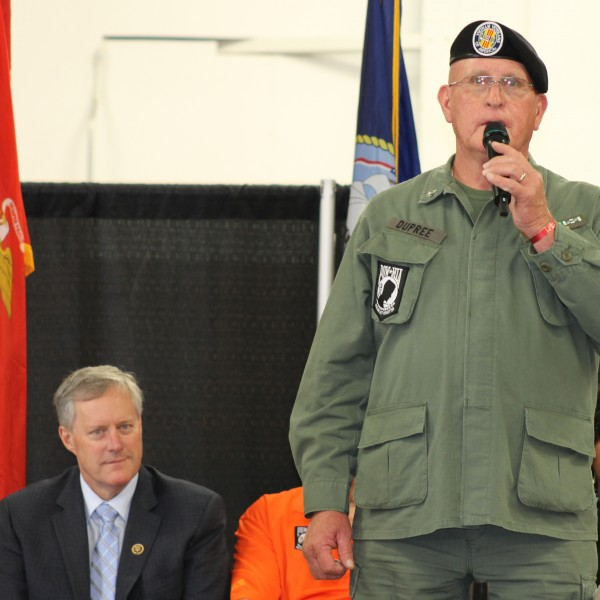 As Congressman Mark Meadows (R-NC) looks on, Warren Dupree (standing), a Vietnam Veteran and Steve Youngdeer American Legion Post 143 service officer, welcomes everyone to an Agent Orange Town Hall meeting on the afternoon of Saturday, Aug. 1 at the Cherokee Indian Fairgrounds.  (SCOTT MCKIE B.P./One Feather photos)