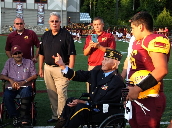 Former Principal Chief Robert Youngdeer tosses the coin at the start of the Braves season-opener against Trinity Academy. Former and present tribal leaders gathered for the coin toss including Former Principal Chief Ed Taylor, Former Vice Chief Pee Wee Crowe, Principal Chief Michell Hicks, and Vice Chief Larry Blythe.