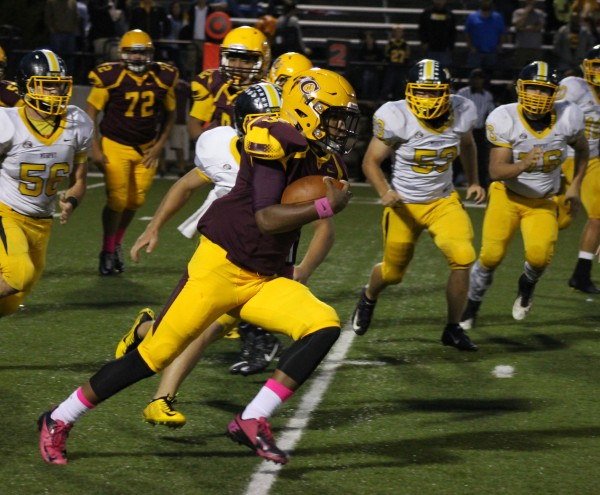 Isaiah Evans (#5), Braves freshman running back, scoots by several Murphy defenders during Friday's home game.  Evans finished the game with 43 yards on 18 carries and he caught 5 passes for 48 yards.  (SCOTT MCKIE B.P./One Feather)