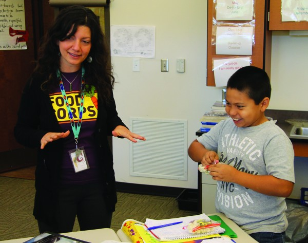 Katie Rainwater, Food Corps, speaks to Ms. Dill's fourth grade class about the nutritional benefits of cauliflower while Hawk Reed opens his snack package containing the vegetable.   (SCOTT MCKIE B.P./One Feather photos)