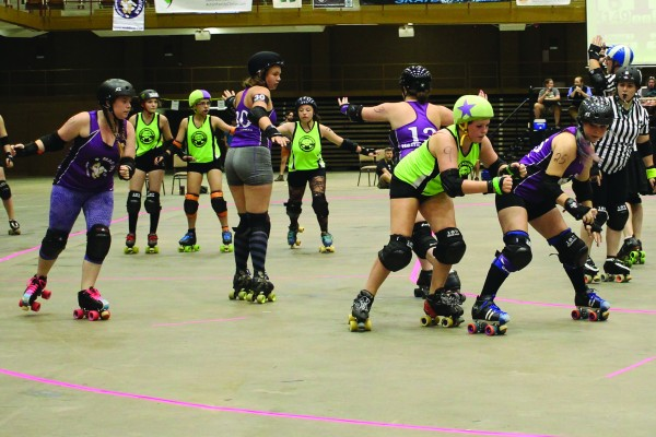 Wearing the jammer star, SMRG's Lil Nemesister Mia Slamm (Rayah Smith) makes her way past one of Asheville's Mad Diva's blockers during a bout in Asheville in July.  The Lil'Nemesisters are set to bout the Atomic City Fallouts from Oak Ridge, Tenn. on Saturday, Sept. 19 at the Swain County Rec. Park.  Three other Nemesisters (green jerseys) form a blocking wall including (left-right) Anne E. Archy (Katy Shackleford), Brings Plenty of Pain (Maleaha Brings Plenty) and Scarlett O'Scara (Alana Booth).  (SMRG photo)