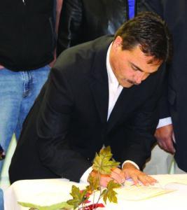 Principal Chief Patrick Lambert signs the legislation.