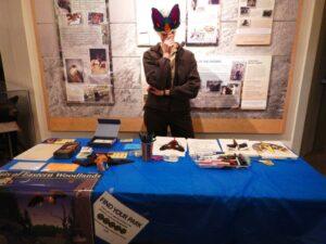 Park Volunteer holds up a paper bat mask at an information station.  (NPS photo)