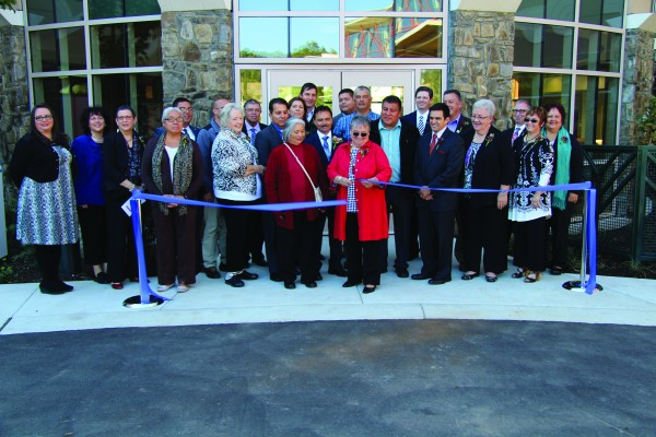 As tribal officials look on, Carmaleta Monteith (center), Cherokee Indian Hospital Governing Board chairwoman, cuts the ribbon to officially open the new Cherokee Indian Hospital on Thursday, Oct. 15.  (SCOTT MCKIE B.P./One Feather photos)