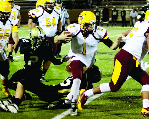 Tye Mintz (#1), Braves sophomore quaterback, eludes two Hayesville defenders on a run during Friday's game. (AMBLE SMOKER/One Feather)