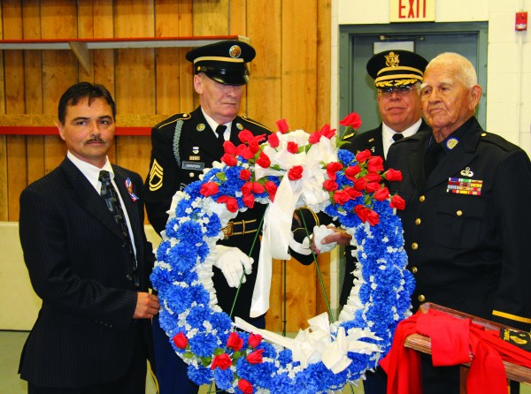 During a Veteran's Day Celebration at the Cherokee Indian Fairgrounds on Wednesday, Nov. 11, Principal Chief Patrick Lambert, SFC Clifford Long, Maj. William Underwood and former Principal Chief Robert S. Youngdeer, a decorated Marine veteran, place a wreath honoring the memory of those who lost their lives in military service. (SCOTT MCKIE B.P./One Feather photos)
