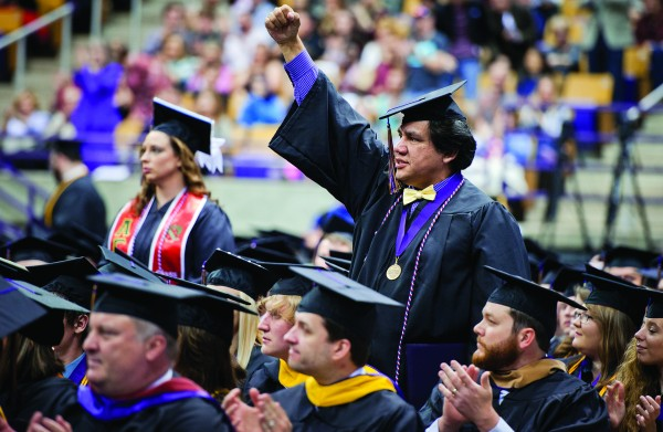 John David Arch Jr., an EBCI tribal member and Navy veteran, is shown standing as the commencement audience recognized graduating students who are active duty members of the military or veterans.