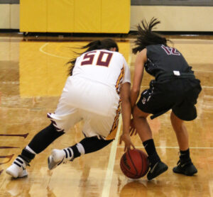 Cherokee's Timiyah Brown (#50) and Swain's Lynsey Hicks ($12) fight for a loose ball near midcourt.