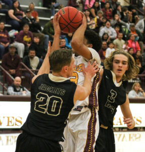 Cherokee's Justus Day (#3) drives between two Hayesville defenders, Braxton Cox (#20) and Owen Gibson (#3), and takes a hard foul from Cox.  Day led Cherokee with 31 points, 2 assists, 5 rebounds and 3 steals.