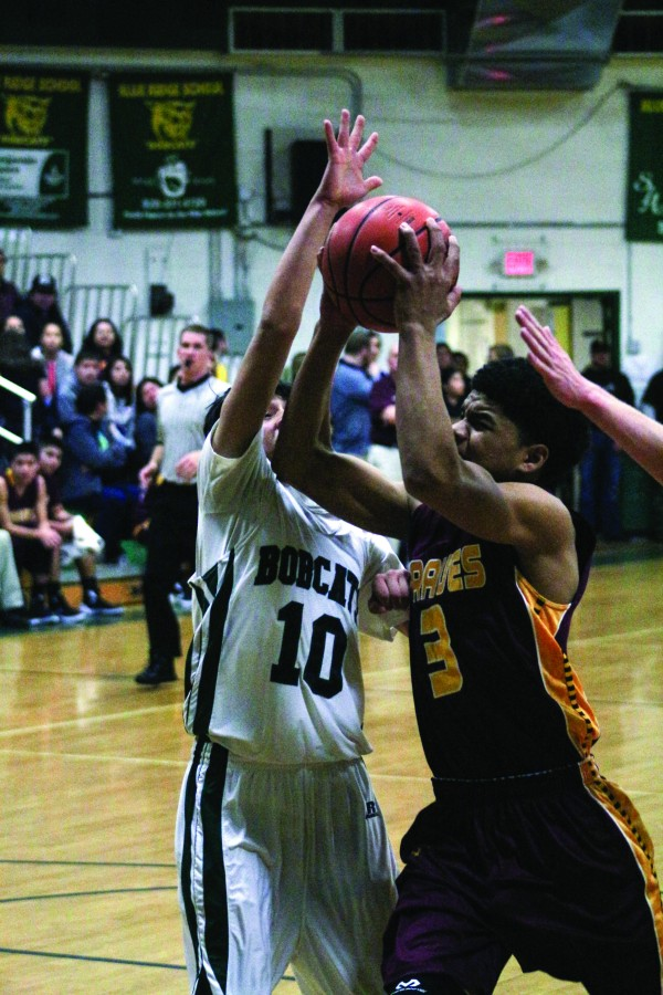 Justus Day (#3), Braves sophomore guard, goes up strong inside against Blue Ridge's Austin Mireles (#10) in Friday's game. Day led Cherokee with 17 points, 2 assists, 3 rebounds and a steal. (SCOTT MCKIE B.P./One Feather photos)