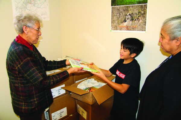 """Myrtle Driver (left), EBCI Beloved Woman, hands a copy of """"Charlotte's Web"""" which she translated into the Cherokee language to her grandson, Taliquo Walker, on Wednesday, Jan. 6 as Painttown Rep. Marie Junaluska, herself a fluent Cherokee language speaker, watches.  (SCOTT MCKIE B.P./One Feather photos)"""