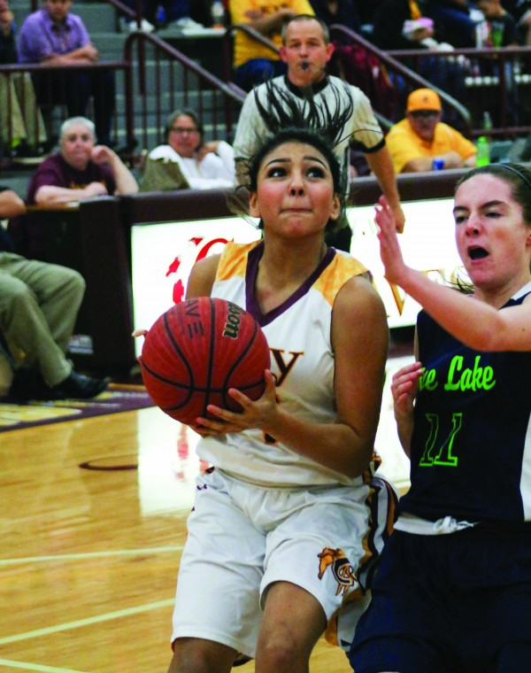 Cherokee's Karla Wolfe (#4) goes for a layup around Pine Lake Prep's Avery Bain (#11) during the first round of the 1A state playoffs on Tuesday, Feb. 23 at the Charles George Memorial Arena.  Wolfe finished the game with 9 points.  (SCOTT MCKIE B.P./One Feather photos)