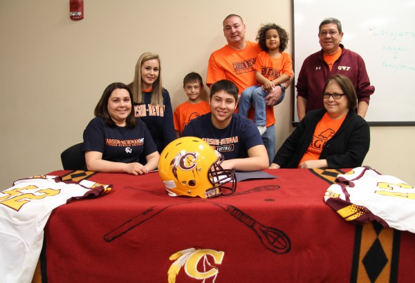 Joined by his family, Logan Teesateskie (center seated), Braves senior linebacker, signs a letter of intent on Thursday, Feb. 4 to play football at Carson-Newman University this fall. (SCOTT MCKIE B.P./One Feather)