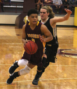 Cherokee's Justus Day (#3) scoots past Hayesville's Owen Gibson in the first half of Friday's game. Day led Cherokee with 32 points, 6 rebounds, 2 assists and 3 steals.