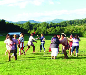 Students in last year's Cherokee History and Culture Institute learn the Cherokee Bear Dance from the Warriors of Anikituwah at the Kituwah Mound site.  (Photo courtesy of Museum of the Cherokee Indian)