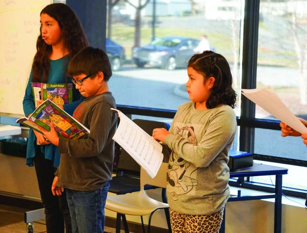 """New Kituwah students Abigail """"Salalisi"""" Taylor, Kallup """"Tsisdu"""" McCoy Jr. and Cameron """"Tsawayagi"""" Jackson practice a song for the school's upcoming production of """"Beauty and the Beast"""" which will be performed entirely in the Cherokee language. (Photo by Renissa McLaughlin/New Kituwah)"""