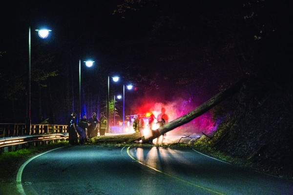Crews work to remove a fallen tree from Acquoni Road on the night of Monday, April 18. Due to some damage caused in the fall, the road will be closed for the next several days from the bridge to the round-about. (Photo by Kristy M. Herron/EBCI Commerce)