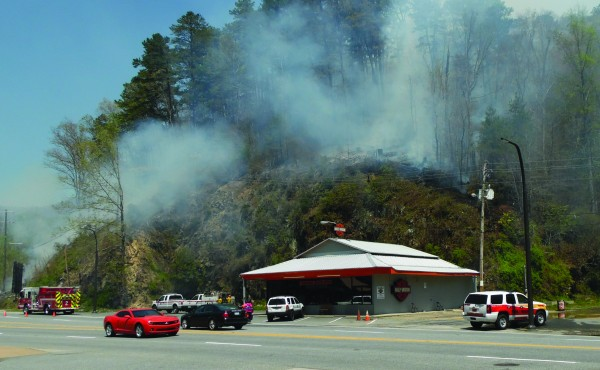 Firefighters work on a smoldering hillside overlooking the Cherokee Harley-Davidson shop in downtown Cherokee on Monday, April 18. (ROBERT JUMPER/One Feather)