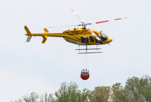 A helicopter heads to a wildfire in the Big Cove Community after picking up water in the pond adjacent to the Cherokee Central Schools on the afternoon of Thursday, April 21. Rain began to fall in the area about four hours after this photo was taken.  (SCOTT MCKIE B.P./One Feather)