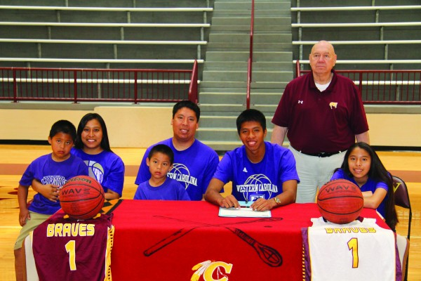 Jason McMillan (seated center), Braves senior point guard, signs a letter of intent on Thursday, May 12 to play basketball this fall at Western Carolina University. (SCOTT MCKIE B.P./One Feather photos)
