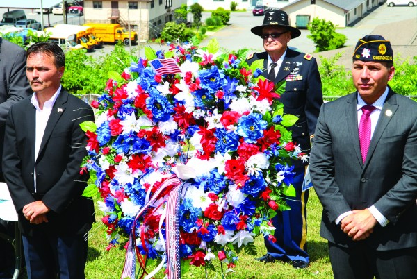 Principal Chief Patrick Lambert, Col. Bob Blankenship (Ret.), and Vice Chief Richard G. Sneed stand at attention following the placing of a wreath in the Yellowhill Veterans Cemetery during a Memorial Day Observance on Monday, May 30. (SCOTT MCKIE B.P./One Feather photos)