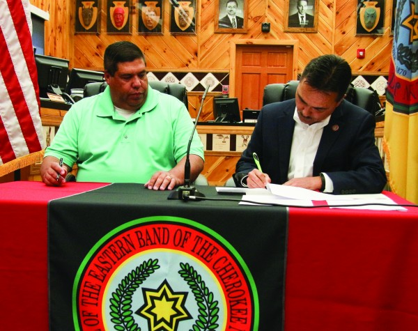 With Tribal Council Chairman Bill Taylor looking on, Principal Chief Patrick Lambert (right) signs a document during a ceremony on Tuesday, May 10 in which the bank notes for the new Cherokee Indian Hospital and the Cherokee Waste Water Treatment Plant were paid in full.  (SCOTT MCKIE B.P./One Feather)