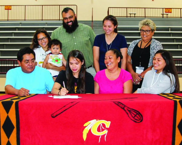 With her family looking on, Le Le Lossiah (seated center) signs a letter of intent on Monday, Aug. 15 to play basketball at Warren Wilson College this winter. (AMBLE SMOKER/One Feather photos)