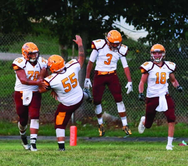 Cherokee's Byron Locust (#70), Will Davis (#55), Shane Swimmer (#3), and Anthony Toineeta (#18) celebrate a 55-yard fumble return for a touchdown by Swimmer in the first quarter.