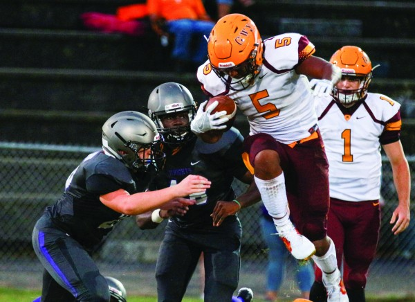 Cherokee's Isaiah Evans (#5), sophomore running back, jumps over the line to avoid two Trinity Academy defenders during Friday's game in Kingsport, Tenn. Evans finished the game with 159 yards and 2 touchdowns on 26 carries. (SCOTT MCKIE B.P./One Feather photos)