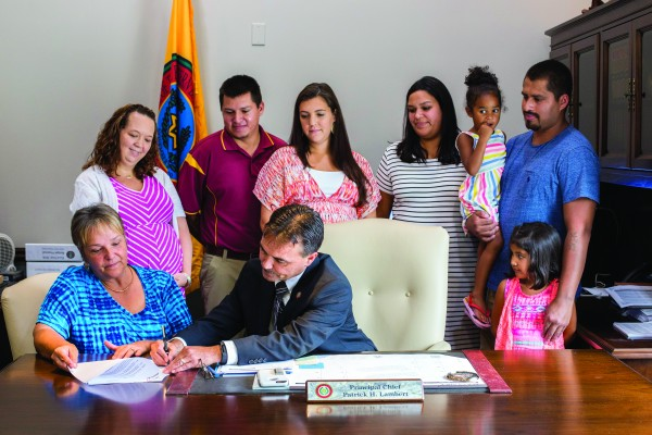 Principal Chief Patrick Lambert (seated right) signs Oosti's Law, which provides additional maternity leave for tribal employees, on Thursday, July 28 as Big Cove Rep. Teresa McCoy (seated left) and others look on.