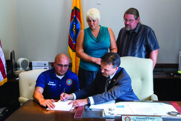 Principal Chief Patrick Lambert (seated right) signs the EBCI Ethics Ordinance into law on Thursday, July 28 as Wolfetown Rep. Bo Crowe (seated left) and Ethics Committee members Sabrina Arch and TJ Holland look on. (EBCI Communications photo)