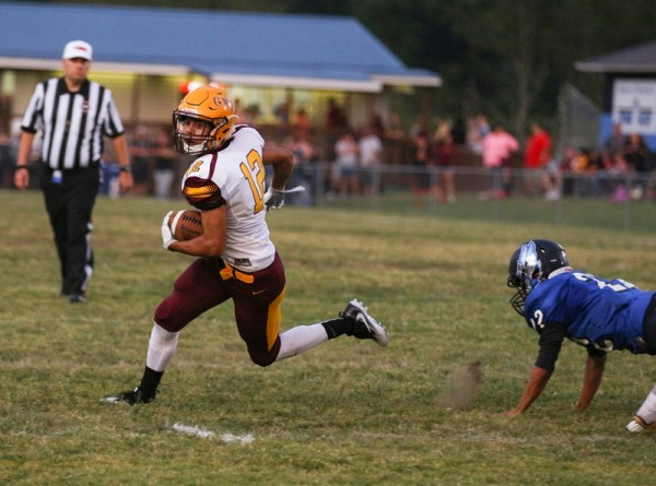 Cherokee's Blake Smith (#12) runs by Cosby's Darien Johnson (#22) en route to a 20-yard touchdown run in the first half. Smith finished the game with five rushes for 77 yards and two touchdowns. (SCOTT MCKIE B.P./One Feather photos)