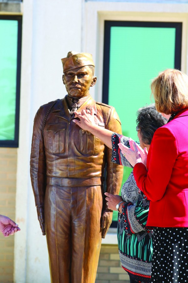 PROUD NIECE: With Cynthia Breyfogle (right), Charles George VA Medical Center director, looking on, Patty Buchanan, George's niece, touches the Medal of Honor medal on the bronze statue. (SCOTT MCKIE B.P./One Feather)