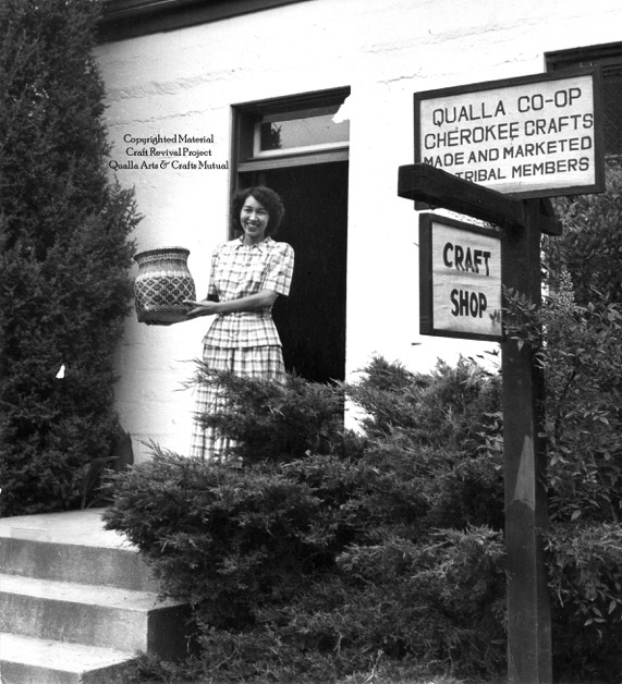 Ethelyn Conseen holds a rivercane basket at the entrance to the Qualla Arts and Crafts Mutual.  (Photo by Clemens Kalischer, courtesy of Qualla Arts and Crafts Mutual)