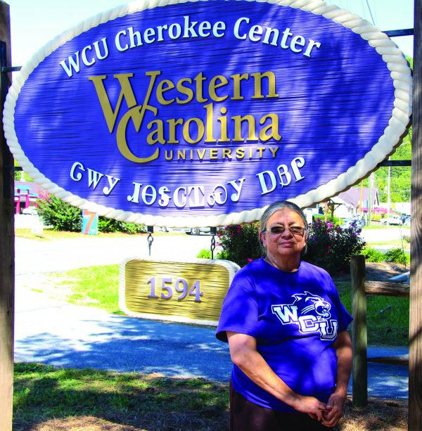 Roseanna Belt, WCU Cherokee Center, stands in front of the Center sign on Friday, Sept. 30 – the day of her retirement from the Center after a 15-year span in the position.  (SCOTT MCKIE B.P./One Feather)
