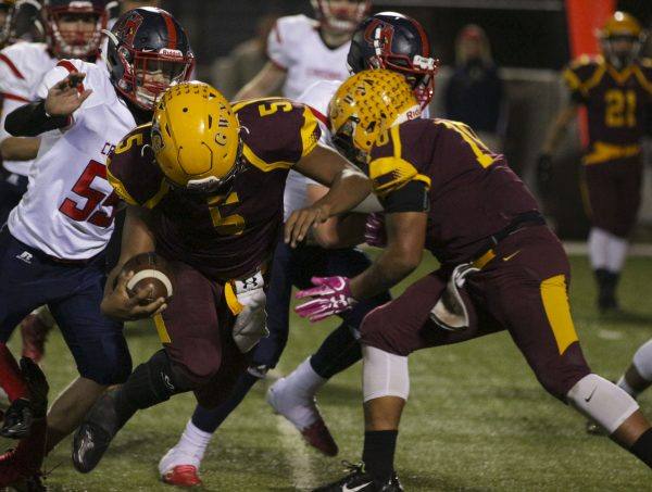 1,000-YARD CLUB: Isaiah Evans (#5), Braves sophomore running back, busts through the line on one of his 27 carries on the night. He gained a total of 140 yards and scored two touchdowns as he surpassed 1,000 yards on the season (1,060).