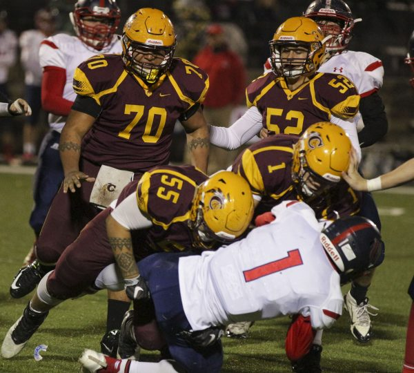 BIG HIT: Will Davis (#55), Braves junior nose guard, gets a good tackle on Manasseh Missick (#1).