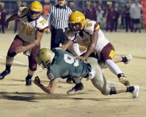 Cherokee's Isaiah Evans (#5) tackles William Archer (#9), Rebels quarterback.
