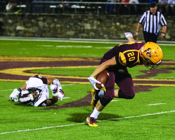 SURE HANDS, FEET: Holden Straughan (#20), Braves junior wide receiver, catches his feet after breaking a tackle following a catch against Swain County on Oct. 7. (SCOTT MCKIE B.P./One Feather)