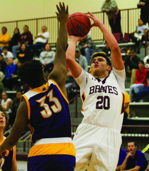Cherokee's Holden Straughan (#20), junior forward, shoots over North Henderson's Tyrek Young (#33) during a game at the Charles George Memorial Arena on Saturday, Dec. 17. The Knights defeated the Braves by a score of 100-79. (SCOTT MCKIE B.P./One Feather)